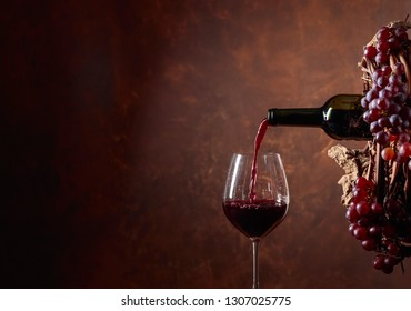Red wine pouring from a bottle into a glass. Wreath of vine with juicy grapes. Conceptual image on the theme of winemaking. Copy space for your text.