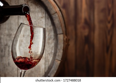 red wine pouring from bottle into glass with old wooden barrel as background