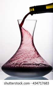 Red wine pouring in decanter.