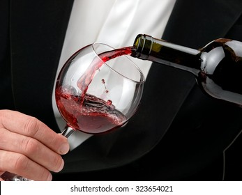Red wine pouring with drops, close up