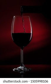 Red wine pouring in a glass from a bottle. Studio shot on black background.