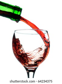Red wine pouring in glass. Isolated over white