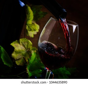 Red wine pouring into a glass, vintage wood background, selective focus