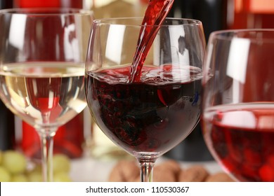 Red wine pouring into a wine glass. Selective focus on the red wine.