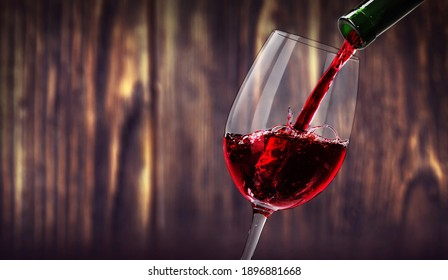 red wine pouring into glass, old wood background