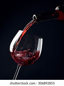 Red wine pouring into wine glass on black background