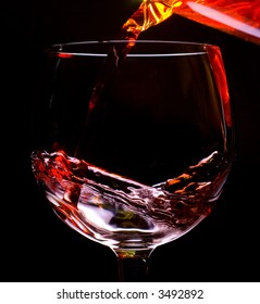 Red wine pouring into a wine glass isolated on black background