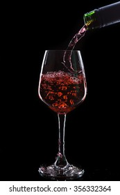 Red wine pouring into a wine glass. Isolated on black background