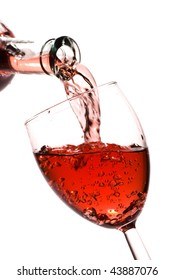 Red wine pouring into a glass isolated on white