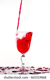 Red wine pouring into a wine glass on white background