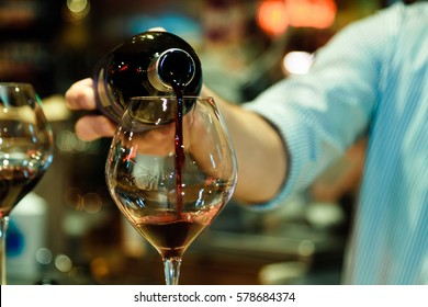 Red wine pouring into a wine glass.