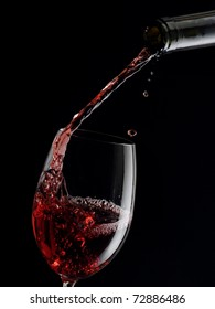 Red wine pouring into a glass with drops on black background