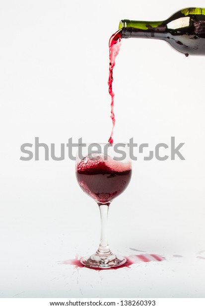 Red Wine pouring out of a bottle into a glass and splattering the white background.