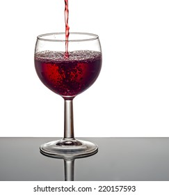 Red wine, pouring. White background. Bubbles and splashes.
