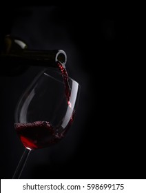 Red wine pouring in wineglass from bottle over black background. Wine list design menu with copyspace. Alcohol beverage card backdrop.