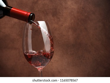 Red wine pouring in wineglass on brown, vintage stone background