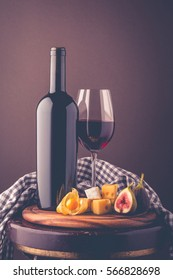 Red wine. Romantic composition from a wine bottle, glass of wine, an appetizer of hard cheese, brie cheese, figs and physalis. Postcard greetings.