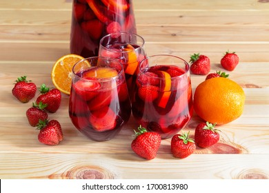 Red wine sangria with fruits in glasses and pitcher and fresh fruits near on wooden table. Selective focus .