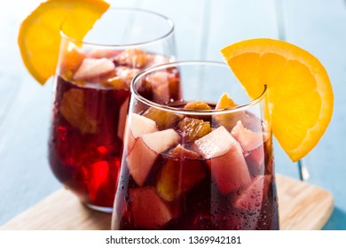 Red wine sangria in glass on blue wooden table.