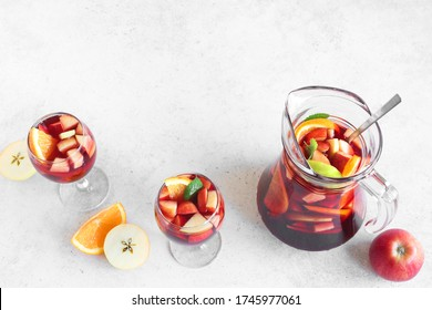 Red Wine Sangria in pitcher and glasses on white table, top view, copy space. Homemade refreshing drink - fruit sangria or punch.