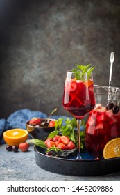 Red wine sangria or punch with fruits and ice in glasses and pincher. Homemade refreshing fruit sangria.