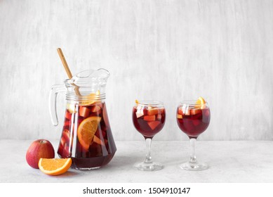 Red wine sangria or punch with fruits and ice in glasses and pitcher. Homemade refreshing fruit sangria on white background, copy space.