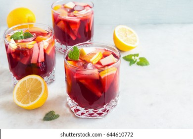 Red wine sangria or punch with fruits, mint and ice in glasses. Homemade refreshing fruit sangria over rustic white table, copy space