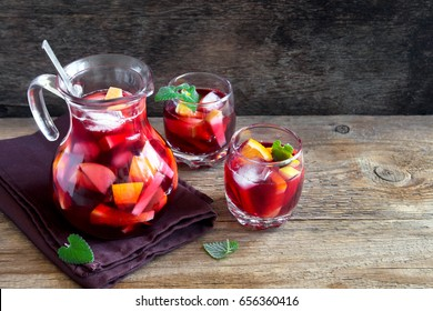 Red wine sangria or punch with fruits and ice in glasses and pincher. Homemade refreshing fruit sangria over rustic wooden table, copy space