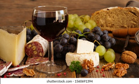 red wine with sausage, cheese, bread and grapes