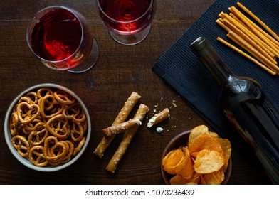 Red wine with savoury party snacks on rustic dark wood background from above.