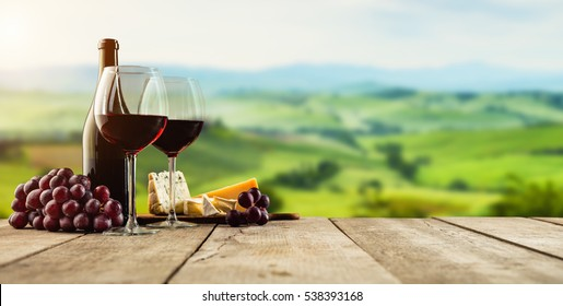 Red wine served on wooden planks, vineyard on background, copyspace for text