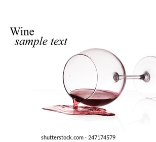 Red wine spilled from glass over white background(with sample text)