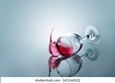 Red wine spilled out of a falling glass reflected on the surface