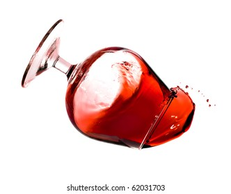 Red wine spilling from a transparent glass isolated on a white background