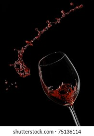 Red wine splash with knots on black background