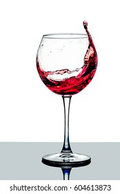 Red wine splashing in a glass on white background