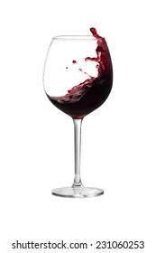 Red wine is splashing out of a wine glass