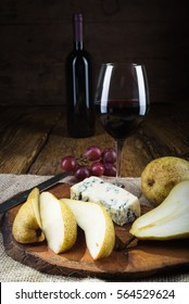 Red wine in vintage light with cheese and fruits.