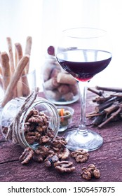 Red wine with walnuts in the foreground. Composition on a wooden table by the window. Crispy sticks, olives and corks from different wines in glass jars on the background