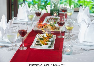 Red wine and white wine served with Thai chicken satay and Pad Thai on the table setting for lunch