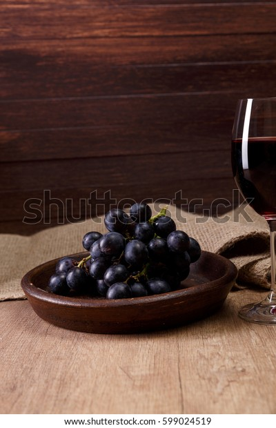 Red wine. Wineglass with dark grapes branch on plate. On rustic wooden background.
