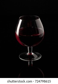 Red wine and wineglass on the black background