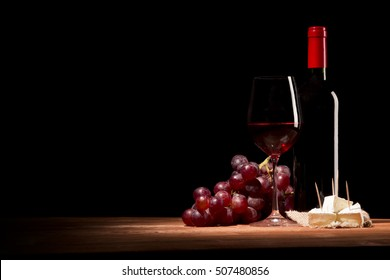 Red wine,cheese and grapes on vintage wooden board