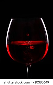 Red wine.Drops of wine fall in glass .Black background