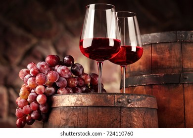 Red wine.Still life two glasses of red wine, grapes and barrel.Selective focus.Wine cellar atmosphere.Copy space
