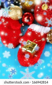 Red winter mittens with Christmas toys on blue wooden table