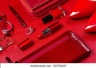 Red woman accessories, jewelry, cosmetic, shoes and other objects on leather background, fashion industry, modern female concept, selective focus