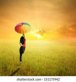Red woman holding multicolored umbrella in green grass field and sunset