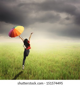 Red woman holding multicolored umbrella in green grass field and raincloud