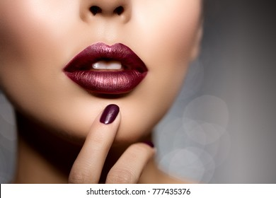 Red woman lips, mouth close up. Beautiful model girl with lipstick plum wine color. Manicure with nail polish Products Treatment